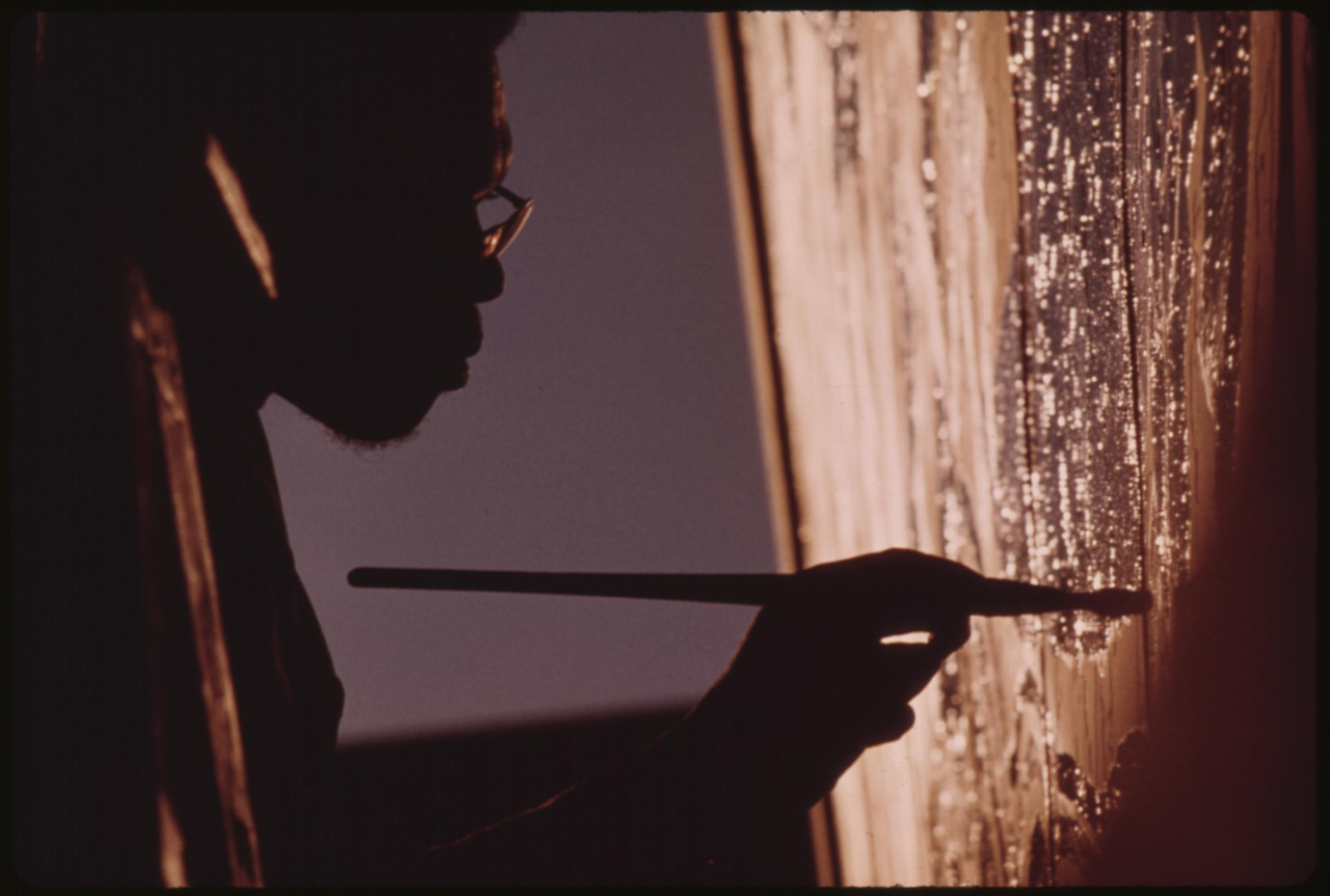 Artist Ron Blackburn painting an outdoor wall mural at the corner of 33rd and Giles Streets in Chicago. 1973.